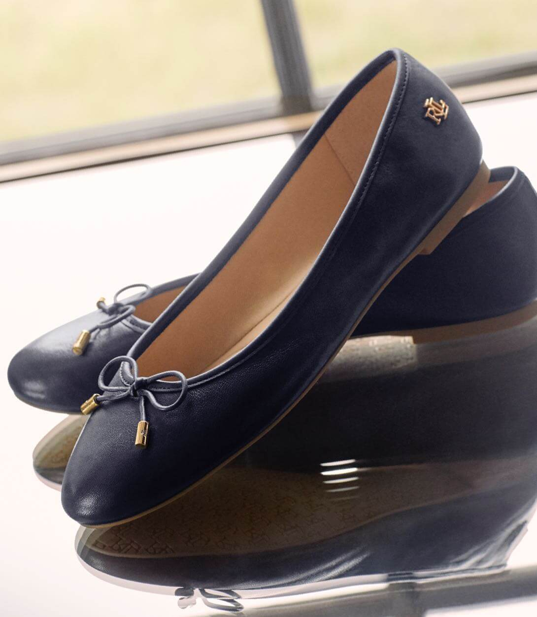 Navy leather flats with ties at the toe.