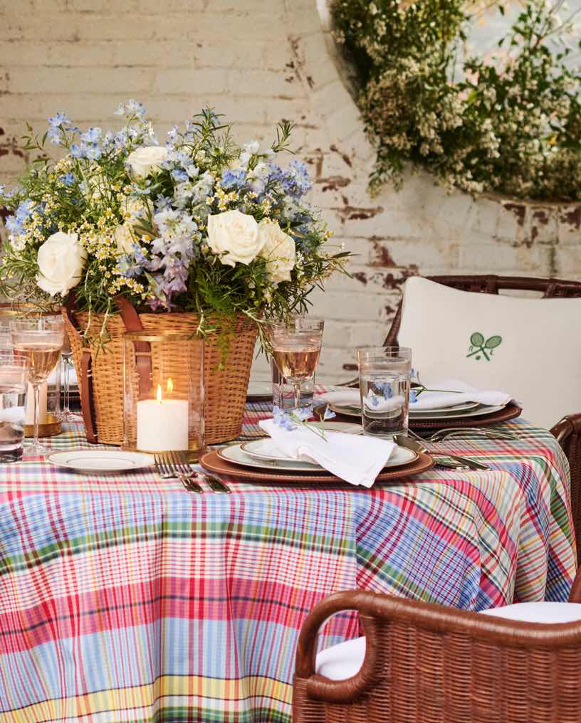 Table set outside with madras tablecloth & wicker chairs