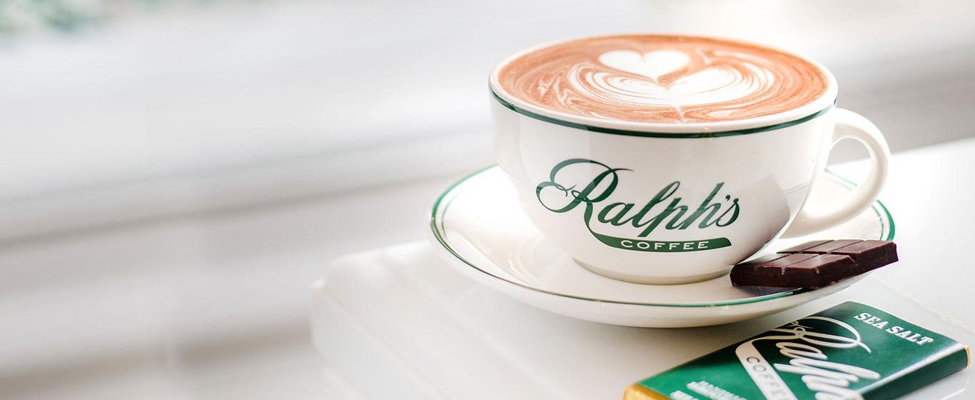Ralph's Coffee mug with latte art, and bar of Ralph's chocolate.
