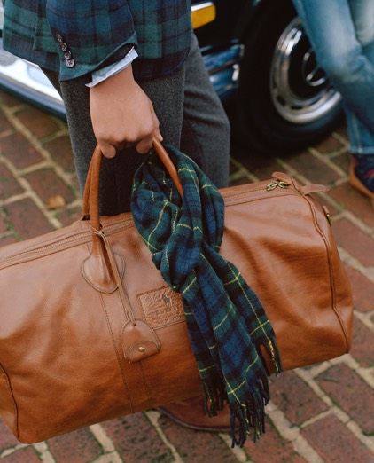Man carrying brown leather duffel bag with two top handles