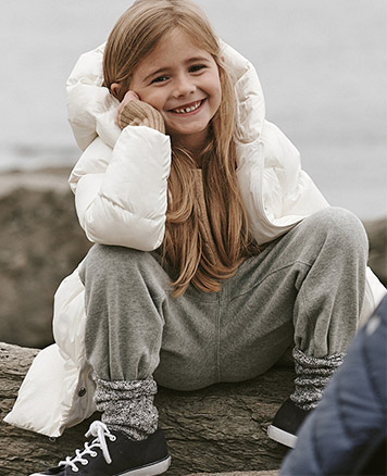 Girl wears long white down jacket with grey sweatpants.