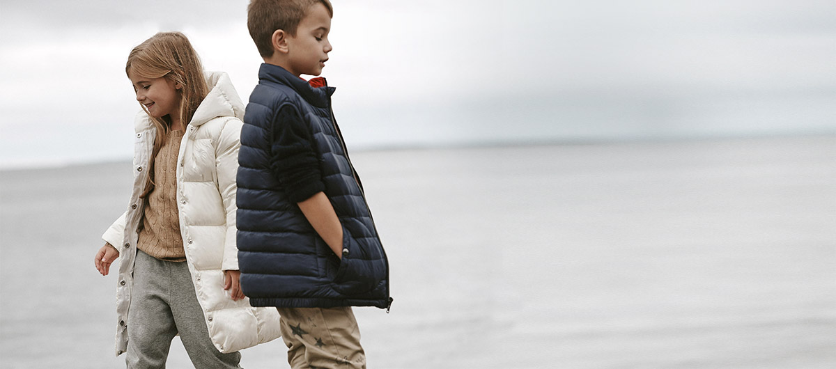 Girl wears white hooded puff coat and sweatpants; boy wears puff vest and chinos.