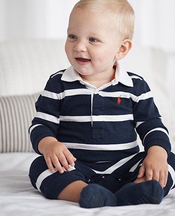 Baby boy wears blue and white striped one-piece.