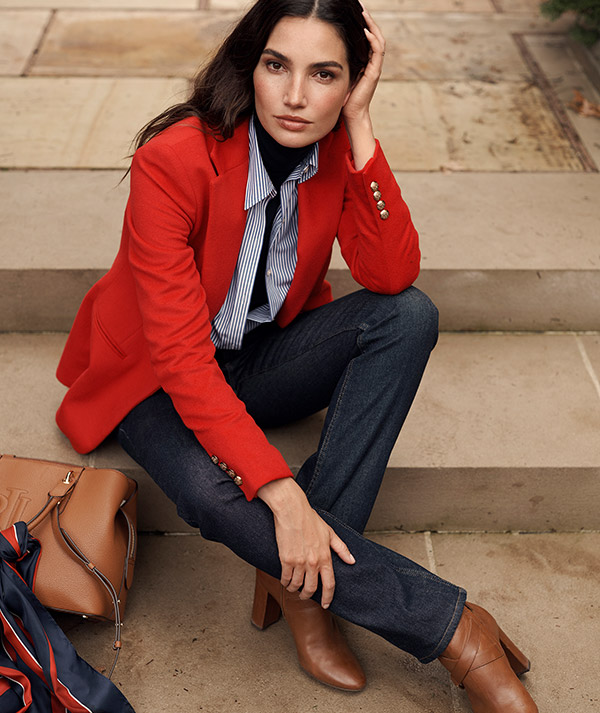 Woman wears orange blazer with striped button-down and dark denim.