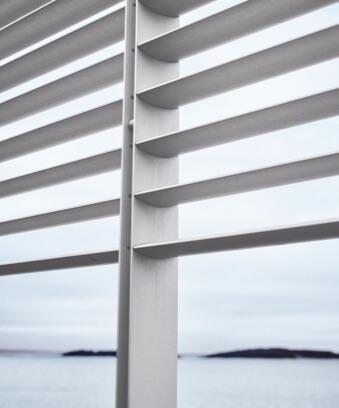 Ocean seen through open white blinds
