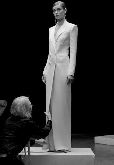 Model getting fitted for white tuxedo jacket–inspired dress