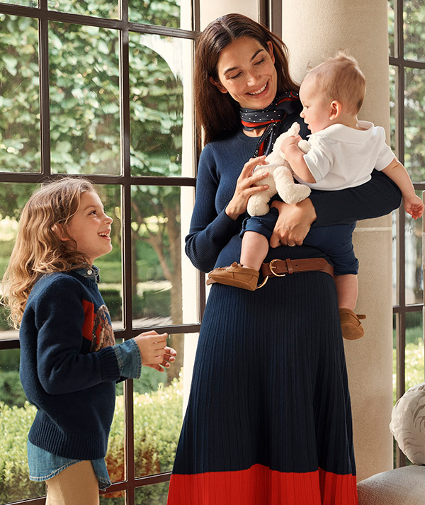 Woman in navy sweater and navy-and-orange pleated skirt holds baby.
