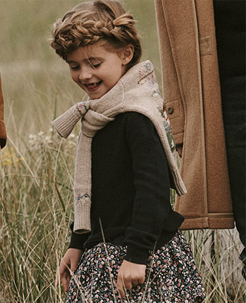 Girl wears sweater with schoolhouse embroidery tied around neck, black sweater, and floral skirt.