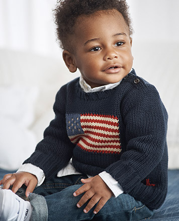 Baby boy wears grey top with Peter Pan collar.
