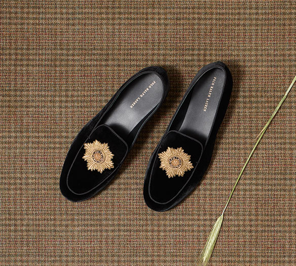 Black suede loafers with gold accent at toe
